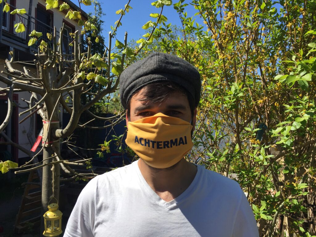 Person mit Maske: ACHTERMAI
