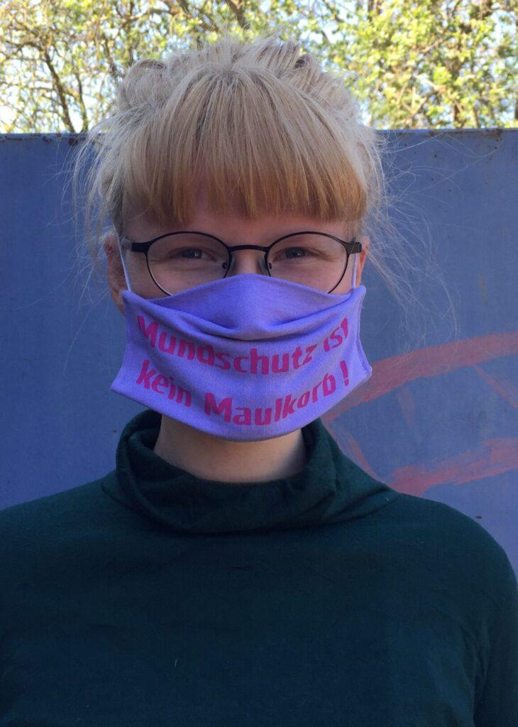 Person mit Maske: Mundschutz ist kein Maulkorb!